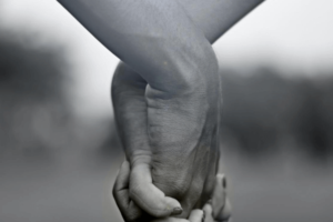 A black and white photo of two people holding hands.