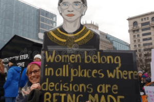 A woman standing at the Women's March and holding a sign with a drawing of Justice Ruth Bader Ginsburg.