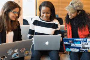 Three women are sitting on a couch while using laptops.