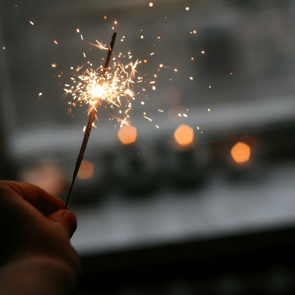 A hand holding a lit sparkler that has a sparkly flame.