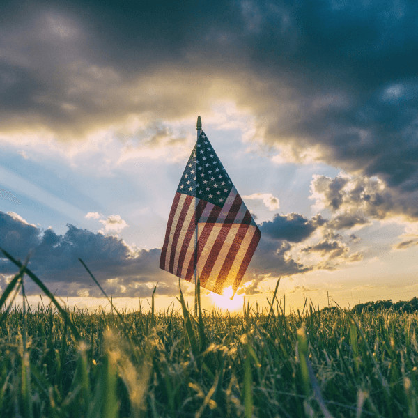 An American flag blowing in the wind in front of a sunset in a grass field