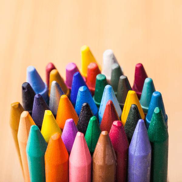 34 crayons of many different colors are tightly arranged in a clumped circle against a peach colored background