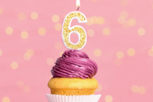 A vanilla cupcake with pink frosting in a white cupcake liner against a pink wall with gold confetti around it. A number 6 candle is lit and placed on the cupcake. The foreground of the photo is lavender.