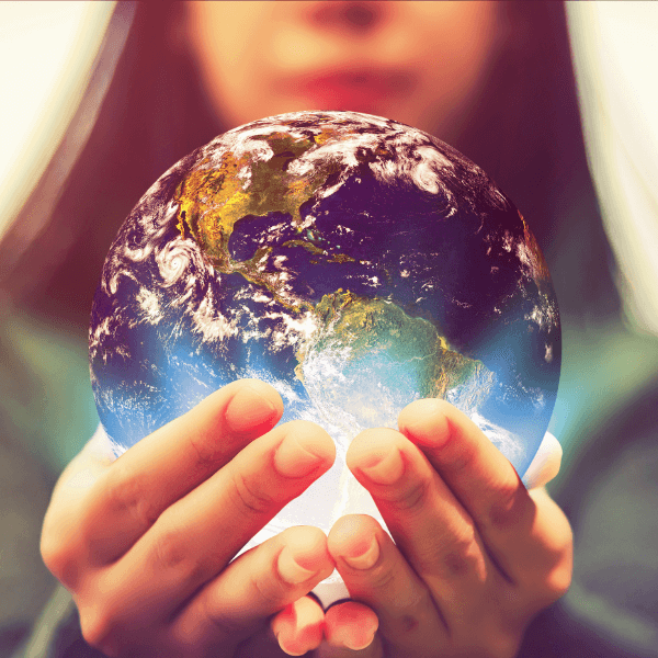 A woman holds a globe that is glowing with light in her hands.