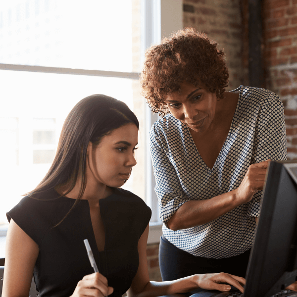 An older woman is standing over a young woman who is working at a computer at a desk. They are in front of windows. The older woman is pointing out something on the computer screen, and the young woman is taking notes.