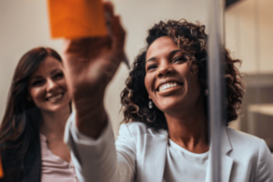 Two women are standing next to each other looking at a Post-It Note. One woman is writing on the orange Post It Note that is posted on a glass wall in their office.
